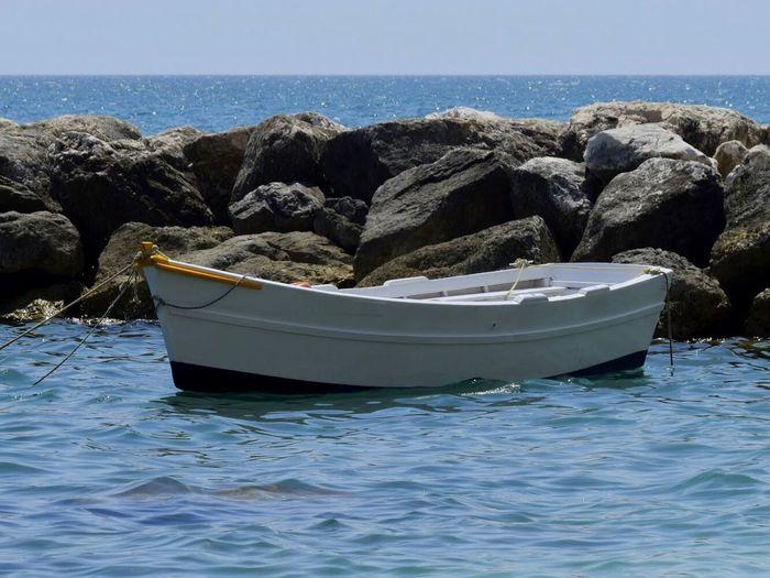 Boat on rocks by sea against sky