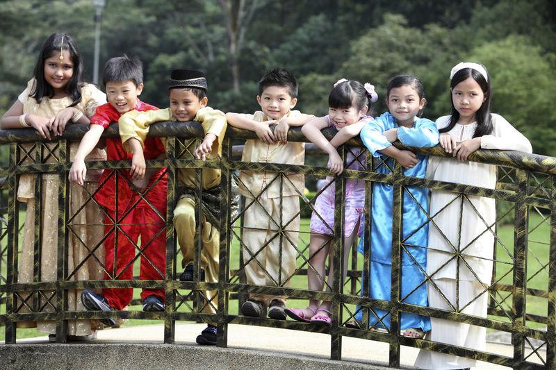 Smiling Friends Standing On Footbridge Against Trees