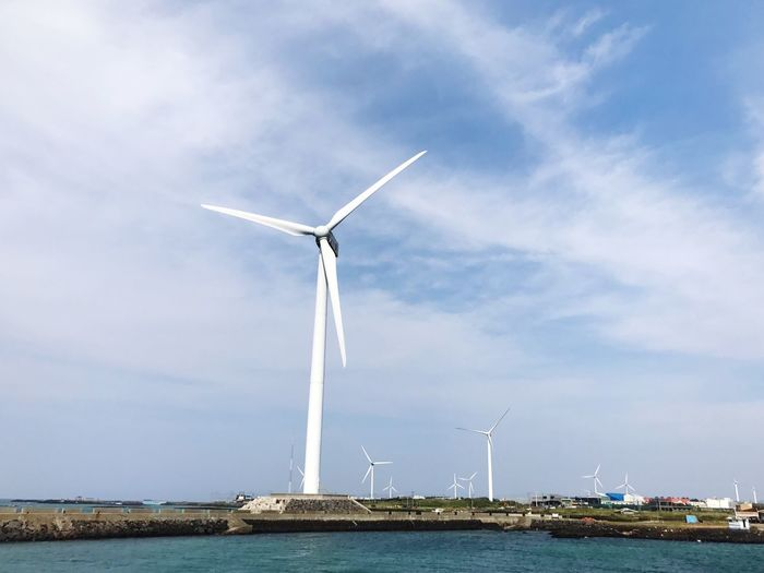 Low angle view of windmills by sea against sky