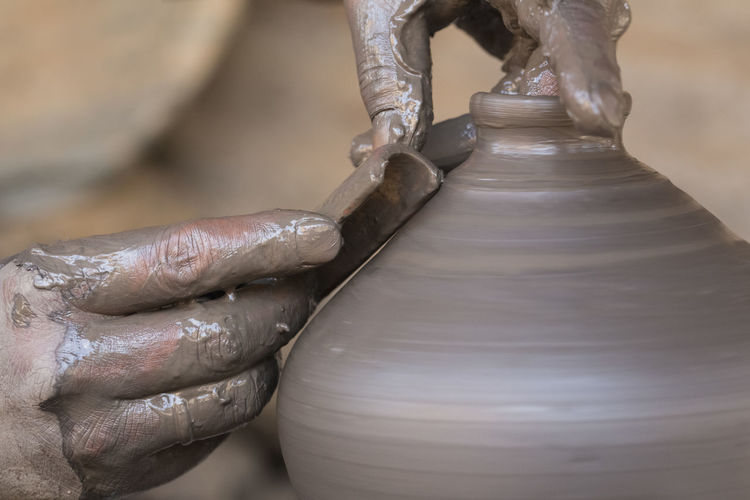 Cropped hands of potter shaping earthenware in workshop