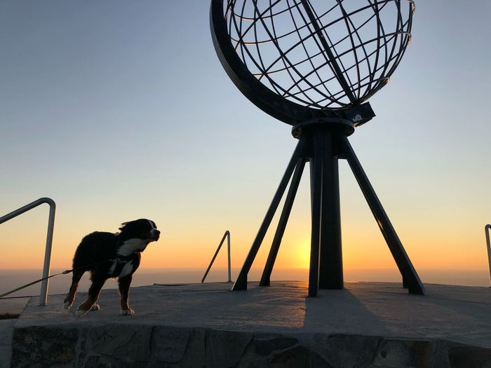 Silhouette dog sculpture against sky during sunset