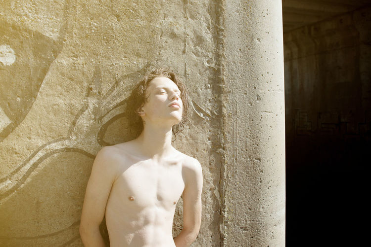 Shirtless man leaning on wall