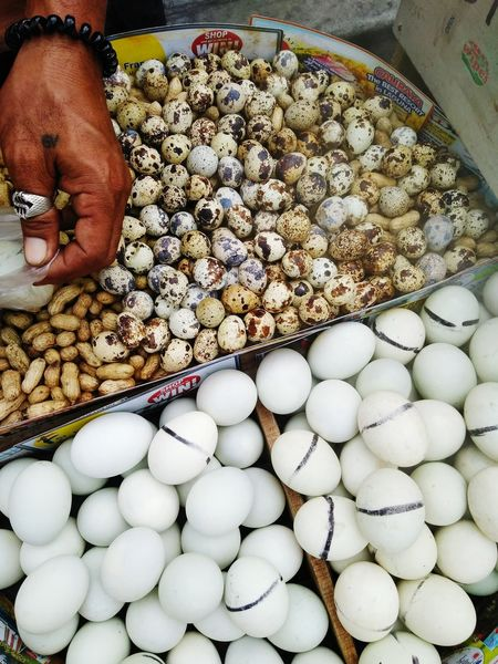 Balut and Penoy Street Food Worldwide Street Food This Week On Eyeem Peanuts Eggs, Balut Penoy Quail Eggs Abundance One Person Large Group Of Objects Food Food And Drink Retail  Outdoors Retail  Egg For Sale People Market Arrangement High Angle View Freshness