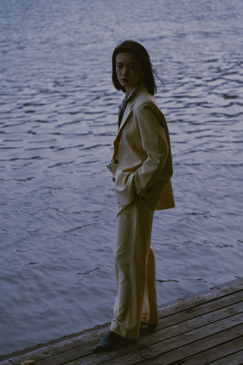 Portrait of woman standing by lake