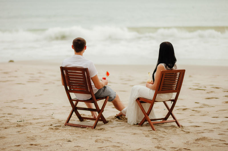 Rear view of couple having drink while sitting on chairs at beach