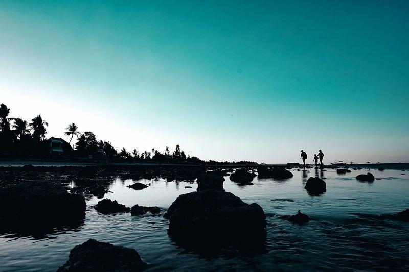 Silhouette Rocks In Lake Against Clear Sky