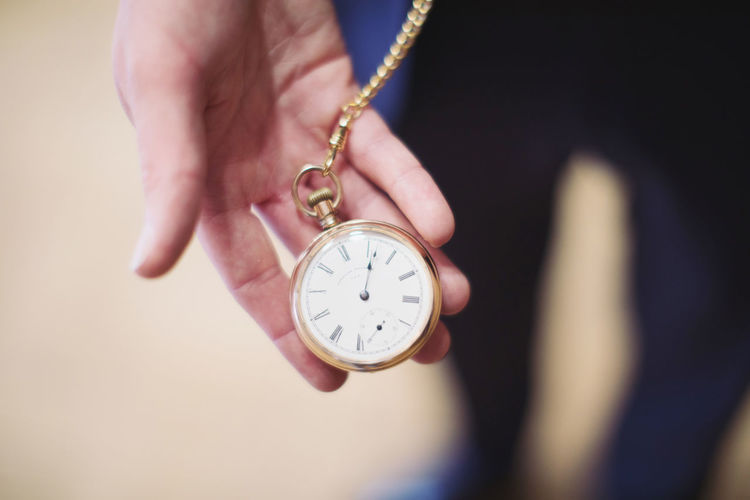 Close-up high angle view of human hand holding pocket watch outdoors