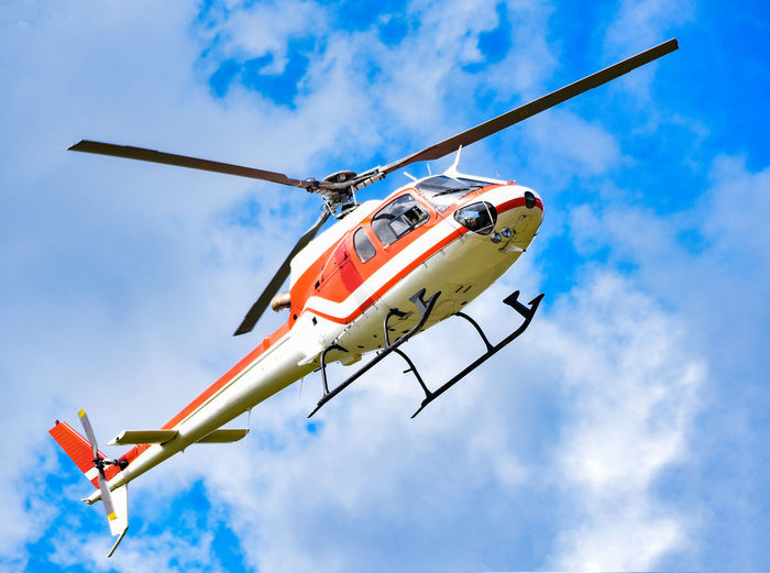 Low angle view of helicopter flying against sky