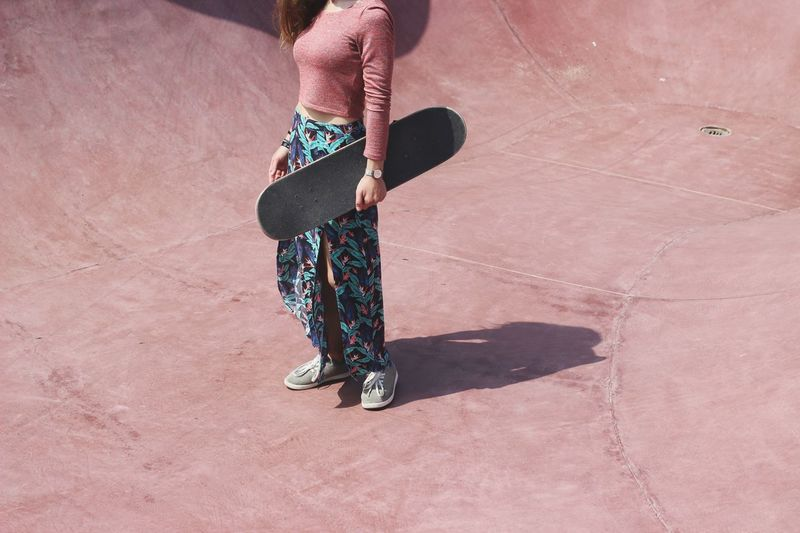 Low Section Of Woman Holding Skateboard While Standing At Skateboard Park