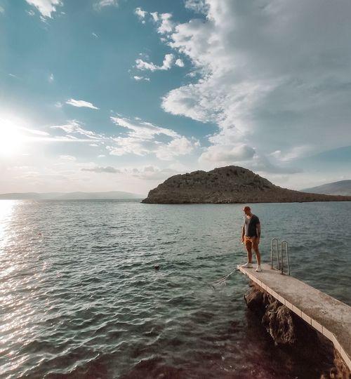 Man standing in sea against sky