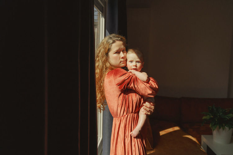 Mother and girl standing at home