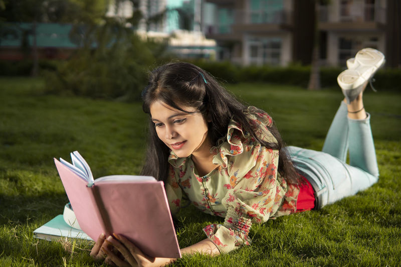 Young woman reading book on field