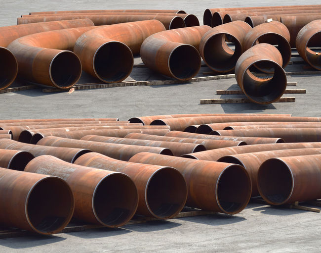 Large rusty metallic pipes on road