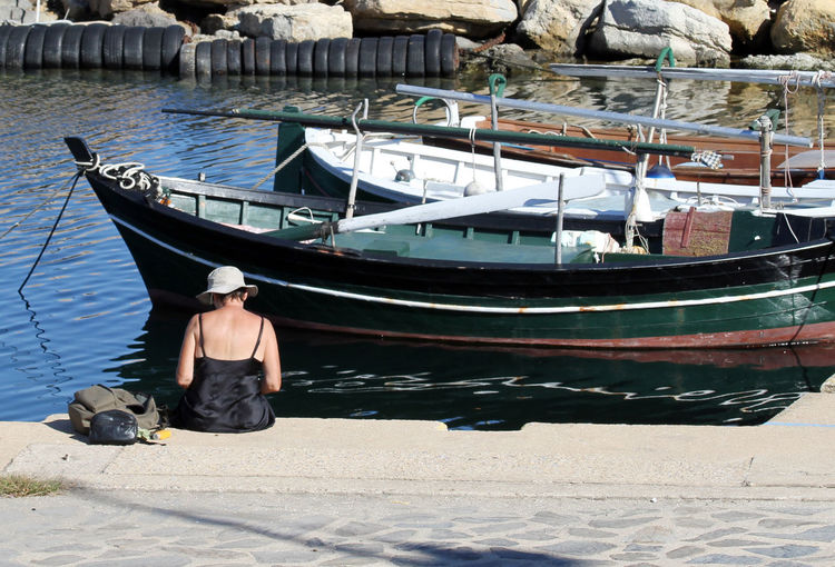 Rear view of woman sitting by boats moored at sea