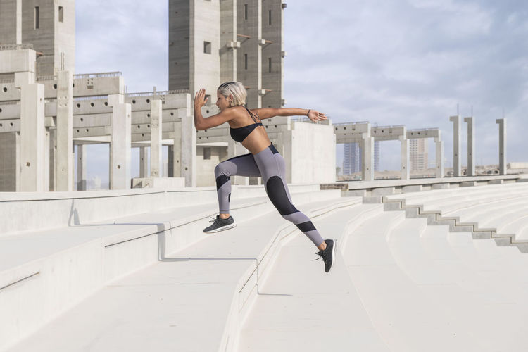 Middle Eastern Girl with short braided hair sprinting up the stairs in a construction site wearing gray and black fitness outfit on a hot bright sunny day. Exercising Jumping Off Rocks Sitting Adult Architecture Arms Raised Bright Day Building Exterior Built Structure City City Life Day Dusty Fitness Model Full Length Hot Day ☀ Human Arm Leisure Activity Lifestyles Middle Eastern Woman Nature Office Building Exterior One Person Real People Sky Sport Sports Clothing Stretching Vitality Women Young Adult