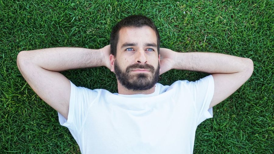 Portrait of young man lying on grassy field
