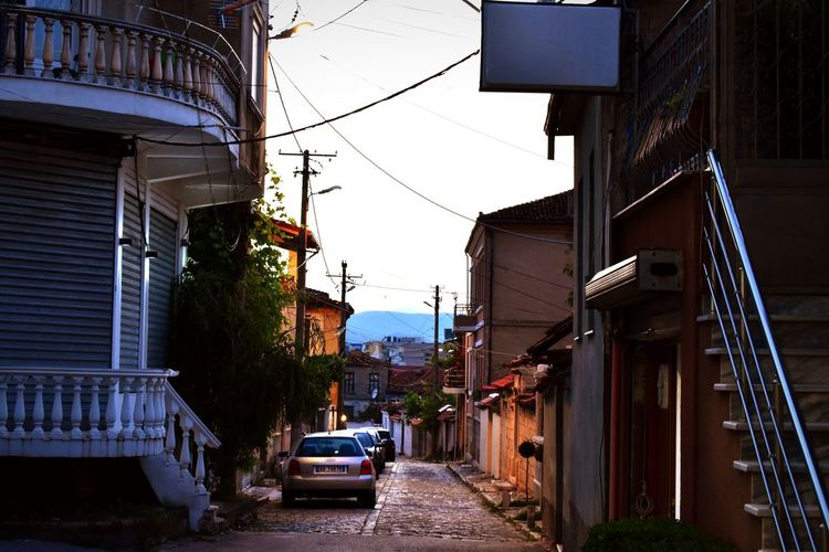 walking the street of Korçë before sunset Blue Light And Shadow Korçë, Albania Small Cities Cities Albania Travel Secret Places Quiet Dusk Calm Vintage Vintage Building City Architecture Building Exterior Sky Built Structure Yellow Taxi Narrow City Street Alley Walkway vanishing point Lane Long The Photojournalist - 2018 EyeEm Awards The Street Photographer - 2018 EyeEm Awards The Traveler - 2018 EyeEm Awards The Architect - 2018 EyeEm Awards