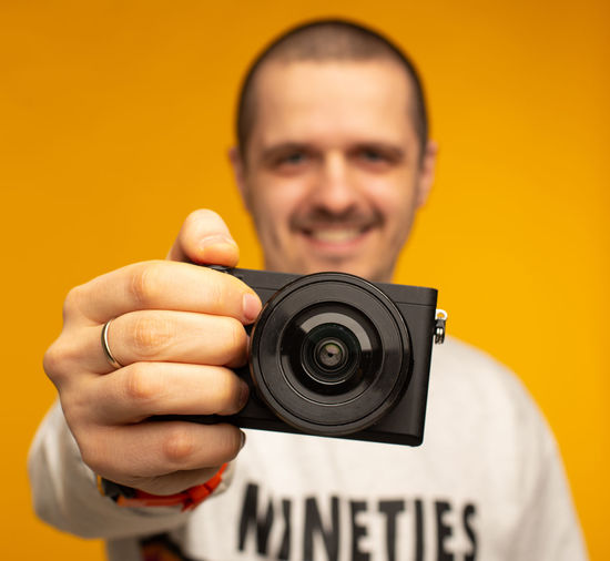 Closeup photo of camera in hand of man photographer who smiling and looking in camera at orange background Portrait One Person Holding Looking At Camera Front View Headshot Men Real People Focus On Foreground Smiling Text Males  Indoors  Yellow Technology Communication Photography Themes Lifestyles Young Adult Young Men Camera Blogger Video Blogging Video Blogs Videographer Photographer