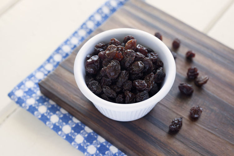 Raisins. Raisins Dried Studio Shoot Selective Focus White Background Indoors  Food And Drink High Angle View Blue Napkin Still Life Close-up Studio Shot Food Napkin Bowl Cutting Board Healthy Eating Table