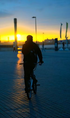 Silhouette man riding bicycle on street against sky during sunset