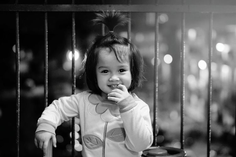Portrait of cute smiling girl with finger in mouth against fence