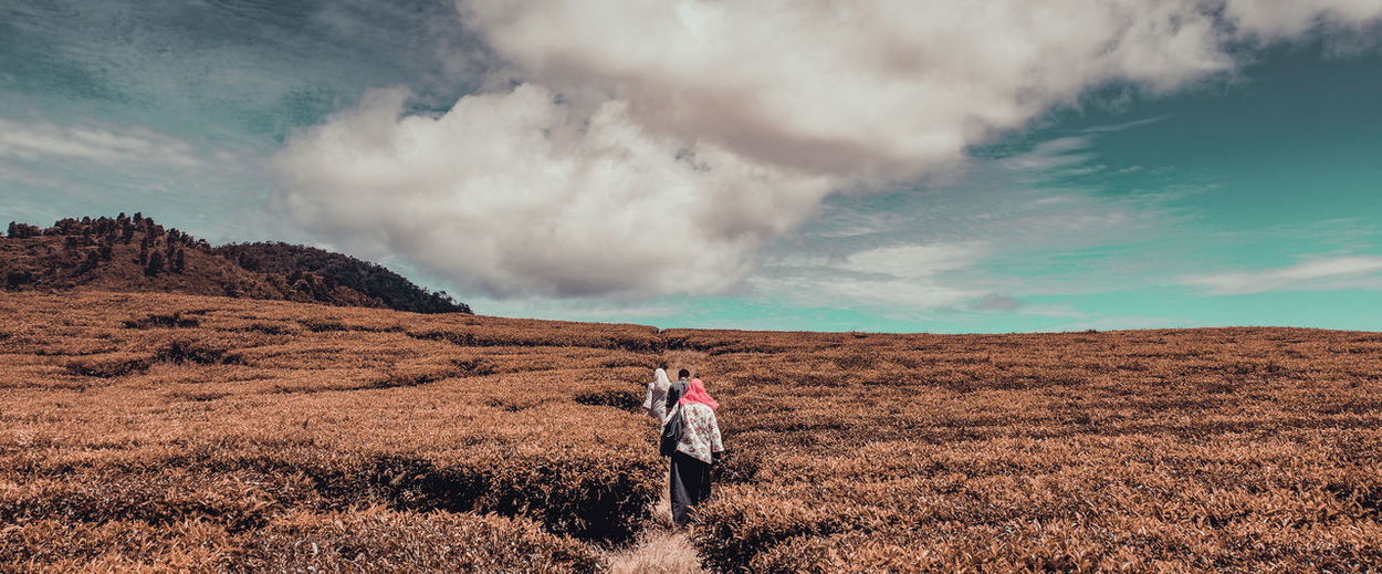 Alahan Panjang Cloud - Sky Land Beauty In Nature Leisure Activity Non-urban Scene Grass Women Field Environment Sky Scenics - Nature Standing Tranquility Adult Landscape Nature Outdoors One Person Rear View Tranquil Scene