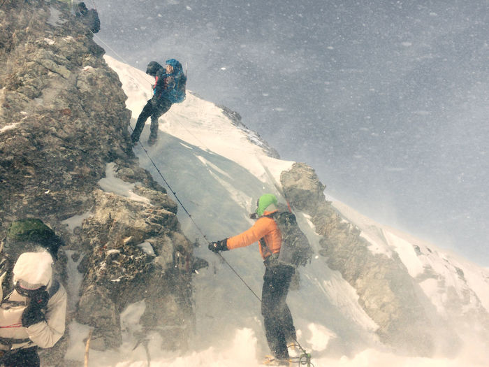 Low angle view of men climbing on snowcapped rocky mountain
