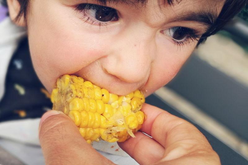 Cropped Hand Feeding Sweetcorn To Child