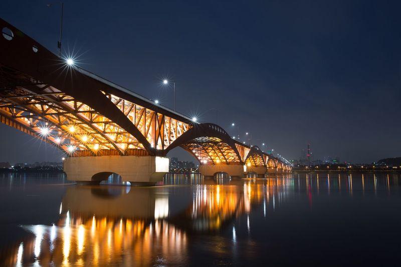 Illuminated seongsan bridge over han river against blue sky at night
