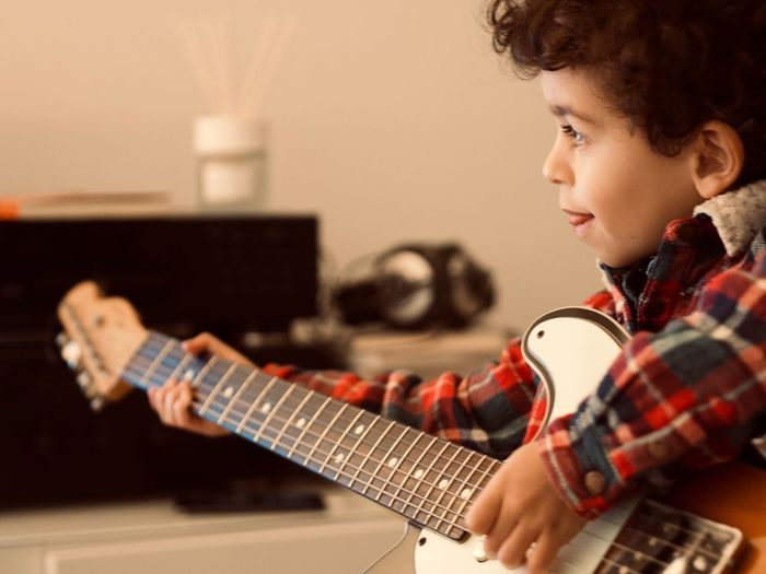 Child Musical Instrument Childhood Music Offspring Indoors  Musical Equipment Boys Playing Guitar String Instrument Men Practicing Males  Headshot Concentration Electric Guitar Guitarist Musician Skill  Plucking An Instrument Profile View