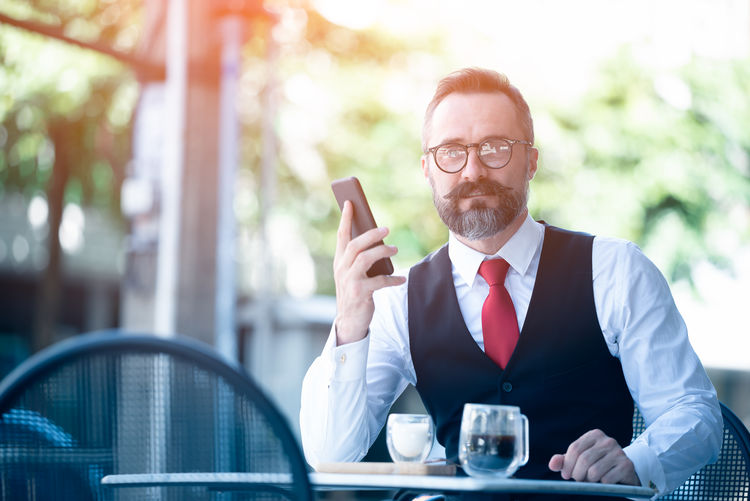 Portrait of man using mobile phone on table