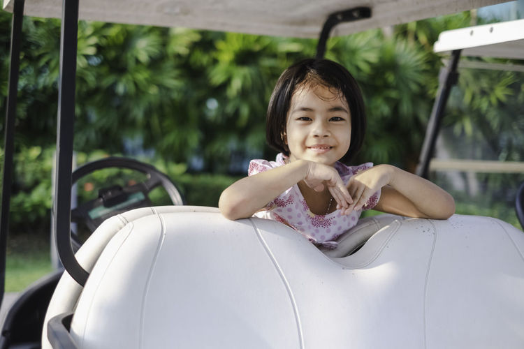 A lovely little girl sitting on a golf cart with her teddy bear. This portrait photo was taken in the park with soft morning light. Adorable kid concept. Child Childhood Real People One Person Lifestyles Leisure Activity Innocence Girl Cute Adorable Lovely Little Golf Cart Vehicle Golfer Teddy Bear Activity Doll Driving Happy Smiling Vacations Young Adult Portrait Playing
