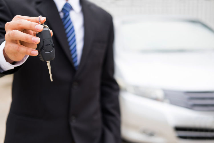 Midsection of salesman holding key while standing against car