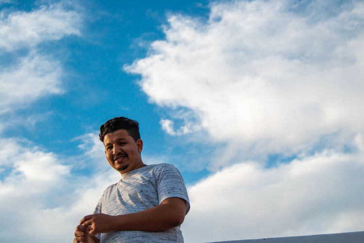 Portrait of smiling man standing against sky