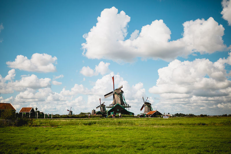 Traditional windmill on field against sky with fluffy clouds