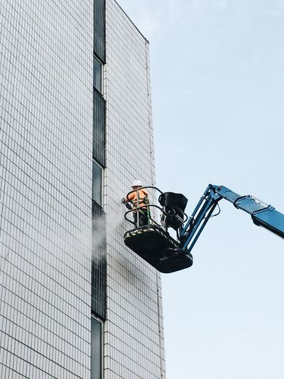 Low angle view of worker cleaning modern building
