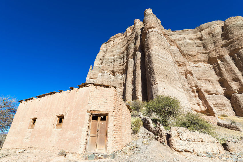 Rustic adobe building at the base of a dramatic cliff in the small town Espicaya near Tupiza, Bolivia Adobe Andean Andes Bolivia Building Color Colorful Country Countryside Desert Destination Formation Full Hills Home Landscape Mountains Nature Remote Rocks South America Travel TUPIZA Valley Village