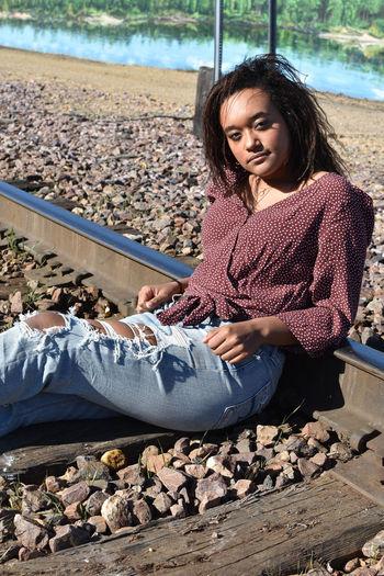 Beautiful young woman sitting at beach