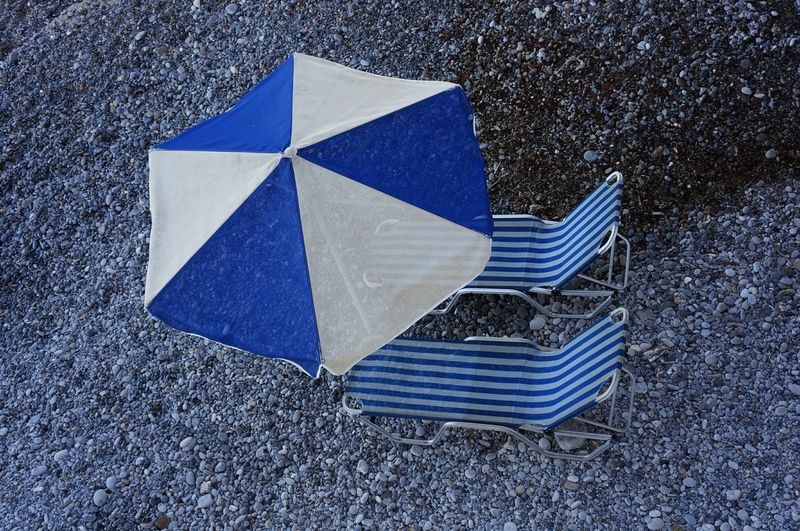 Umbrella and chairs on pebble beach