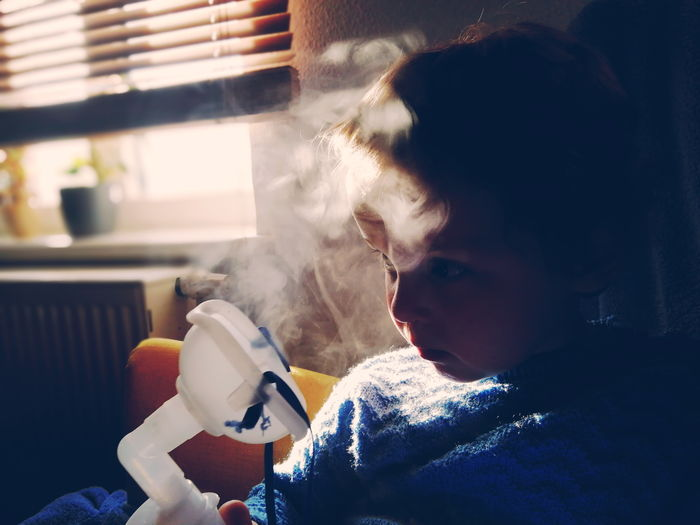 Boy inhaling vapor at home