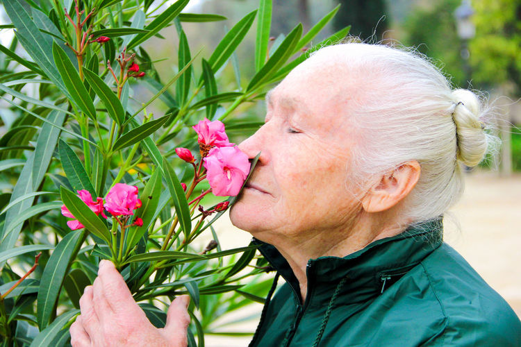 Pretty elderly woman smelling pink flowers on a bush outside during spring Plant Flower Flowering Plant Headshot Close-up Beauty In Nature Lifestyles Freshness One Person Women Portrait Fragility Nature Growth Vulnerability  Real People Leisure Activity Adult Inflorescence Petal Pink Color Flower Head Outdoors Human Face Senior Adult Senior Women Smelling Smelling The Flowers Elderly Elderly Woman Flowers Pensioner My Best Photo My Best Photo The Portraitist - 2019 EyeEm Awards