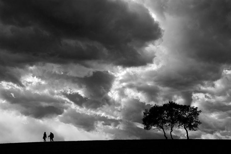 Two silhouette are walking under stormy cloudy weather. Cloud - Sky Sky Silhouette Nature Environment Tree Beauty In Nature Land Landscape Scenics - Nature Storm Plant Horizon Over Land Overcast Field Tranquility Tranquil Scene Thunderstorm Horizon Outdoors Ominous