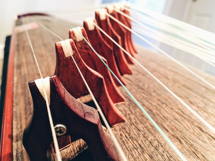 Guzheng - traditional Chinese zither. Guzheng Zither Guzheng No People Close-up Day High Angle View In A Row Focus On Foreground Still Life Metal Musical Equipment String Instrument Music Selective Focus Arts Culture And Entertainment Indoors  Musical Instrument Wood - Material Sunlight Shadow Nature