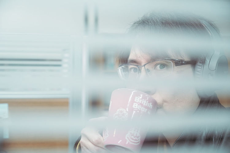 Portrait of man holding glass window
