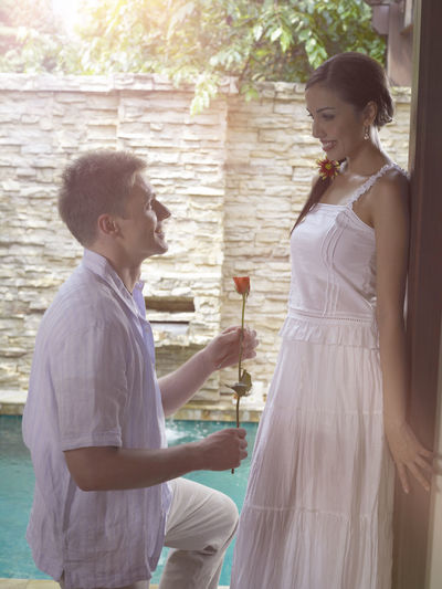 Man Kneeling While Proposing Woman With Red Rose By Swimming Pool