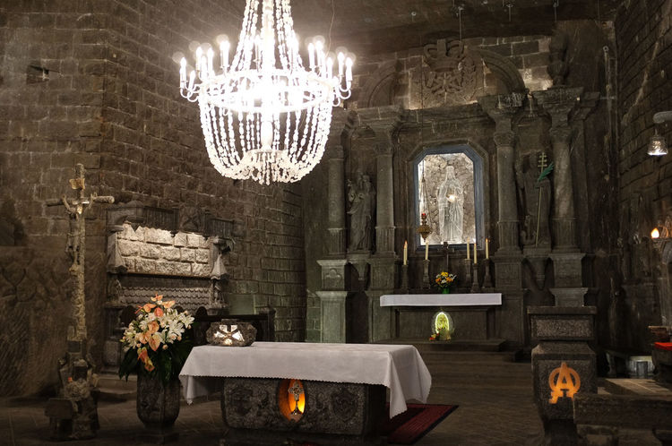 Church and alter carved from salt at Wieliczka Salt Mine in Krakow Poland Salt Salt Mine Wieliczka Salt Mine Altar Candle Carved Chandelier Hanging Illuminated Indoors  Krakow Lighting Equipment No People Religion Spirituality Statue Table Vase