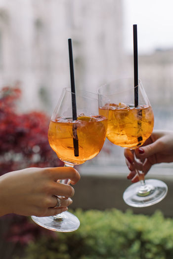 Holding Drink Refreshment Human Hand Alcohol Human Body Part Hand Food And Drink Focus On Foreground Glass Celebration Real People Close-up Celebratory Toast People Drinking Glass Adult Lifestyles Women Wine Cocktail Human Limb Finger Aperitif Aperol Spritz Orange Color Outdoors Summer
