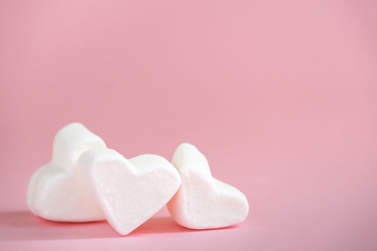 Close-up of heart shape over pink background