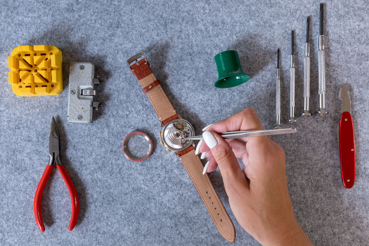 Cropped Hand Of Woman Repairing Wristwatch On Table
