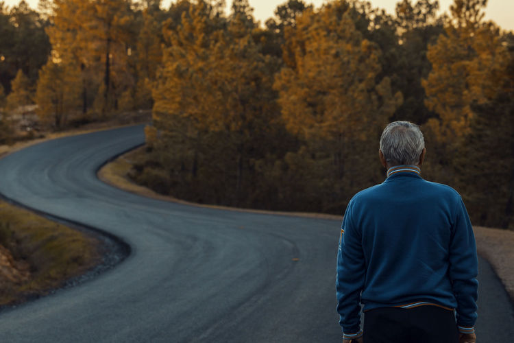 Rear View Of Senior Man On Road Amidst Trees During Autumn